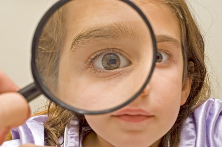 exaggerate: Young girl and magnifying glass LANG_EVOIMAGES