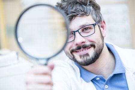 Optometrist holding magnifying glass