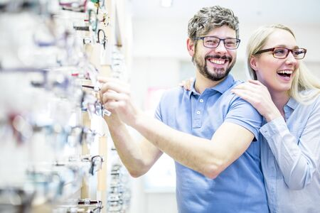 Couple laughing near glasses rack