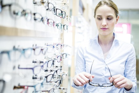 Woman holding glasses near glasses rack in optometrists shop LANG_EVOIMAGES