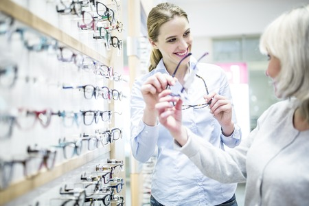 optician: Smiling optometrist helping patient shopping for new spectacles