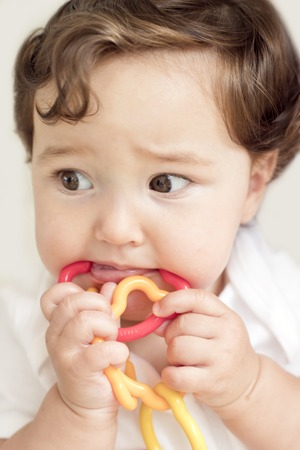 teething: Female toddler chewing rattle