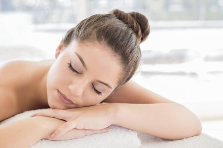 Woman lying on towel in spa LANG_EVOIMAGES