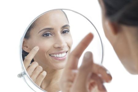 in vain: Woman looking in mirror, smiling