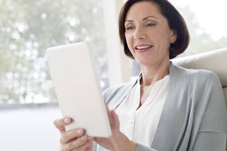 Mature woman using digital tablet