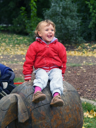 Little girl siting on wooden statue of sheep in outdoor playgraud Stock Photo - 8763764