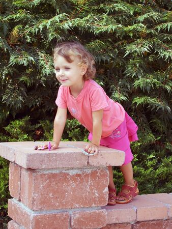 Little girl staing on the fence wall Stock Photo - 8980529