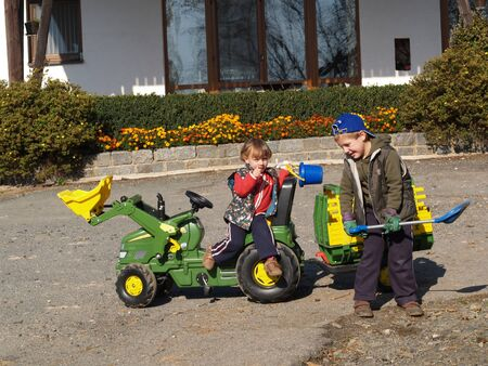 Boy and girl playing with toy tractor