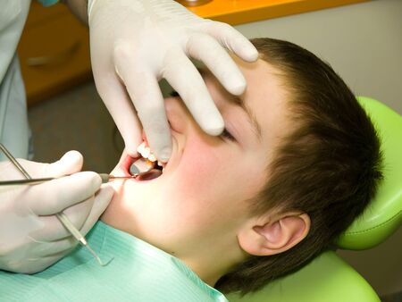 Young boy under dental preventional examination photo