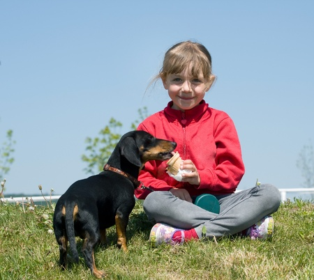 Little girl eating icecream with her dog Stock Photo