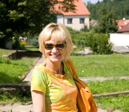 Satisfied woman in orange on summer walk Stock Photo