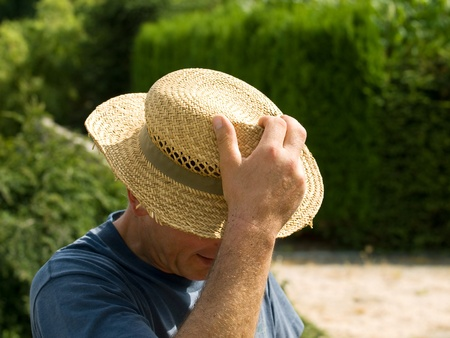 Men taking off his straw hat