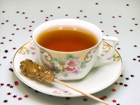 Cup of tea with sugar stick in antique crockery photo