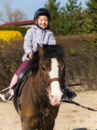 Happy little girl riding on ponny horse photo