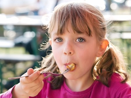 Preschool girl eating snacks Stock Photo