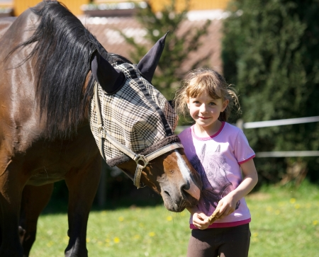 Girl with horse in protective mask