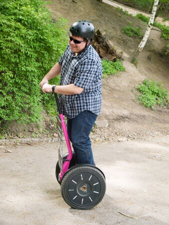 Mature man driving on segway Stock Photo