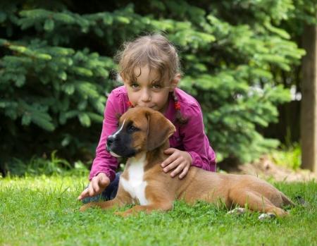 Girl kissing her lying puppy