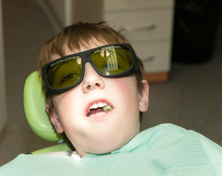 Boy waiting for laser treatment in dental office photo