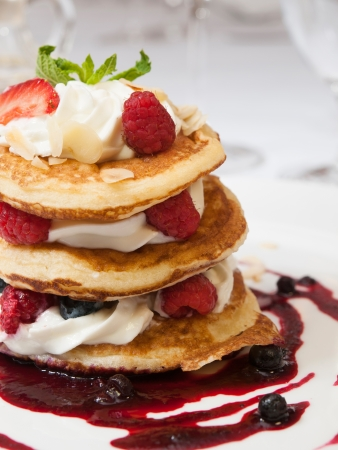 Crumpets with raspberry sauce , whipped curd cheese and roasted almonds