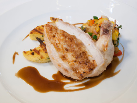 Grilled supréme of farm chicken with roasted vegetables and herb polenta  Stock Photo