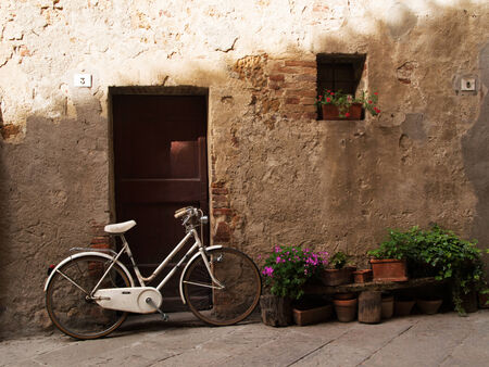 Retro white bycicle against the door in Italy