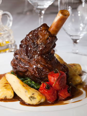 the lamb: Lamb knuckle with thyme gravy, roasted potato sticks (dumplings) and spinach leaves Stock Photo