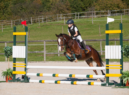 Girl and pony jumping over hurdle on showjumping competition