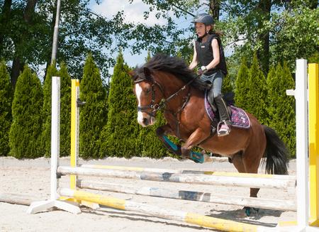 hurdle: Young girl practising jumping over hurdle