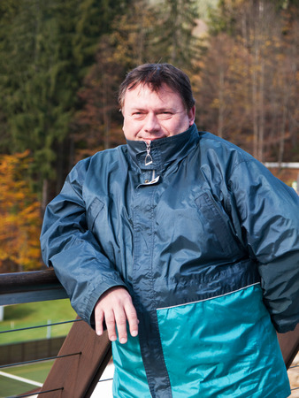 Portrait of mature man in jacket on teracce in autumn photo
