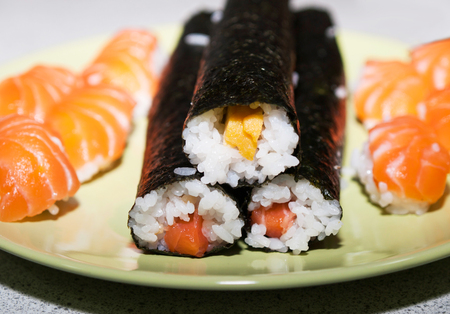 Traditional japanese sushi with salmon and eggs prepared forcut it into portions