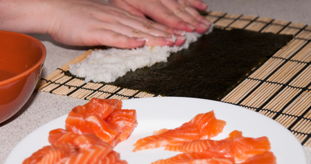 Woman preparing rice on seaweed to wrap it into sushi roll Stock Photo