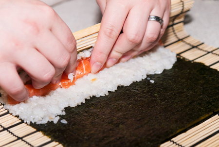 Woman prepared traditional japan sushi rolls with salmon Stock Photo