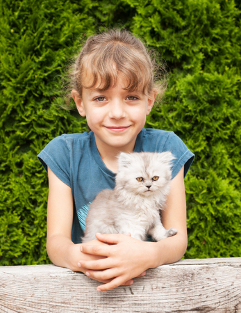 Portrait of little girl and her kitten of persian cat