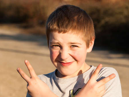 Portrait of boy showing victory gesture photo