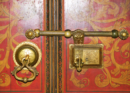Historical golden lock and doorknocker on red door with gold decoration
