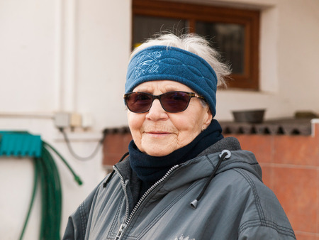 Portrait of satisfied eighty years old woman with sunglasess