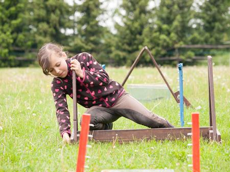 Young girl preparing hurdles for rabbits photo