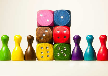 Multicolored wooden game dices with six numbers and pawns Stock Photo