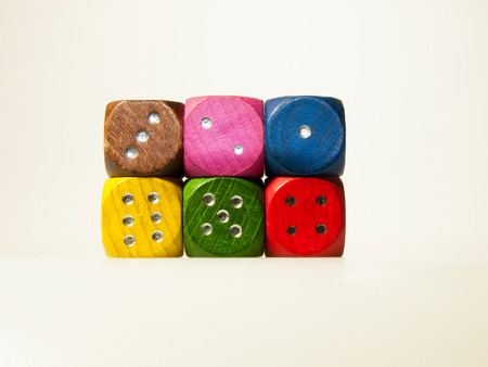 Isolated wooden game dices with numbers in six colors