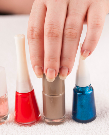 Detail of hand choosing  between various color of nail polishes