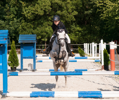 Girl with roan pony jumping over the hurdle on showjumping competition photo