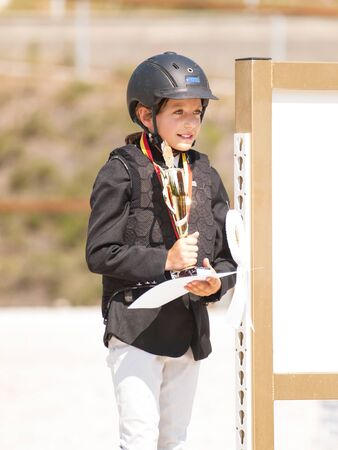 Young girl with cup and medal after winning equine competition photo
