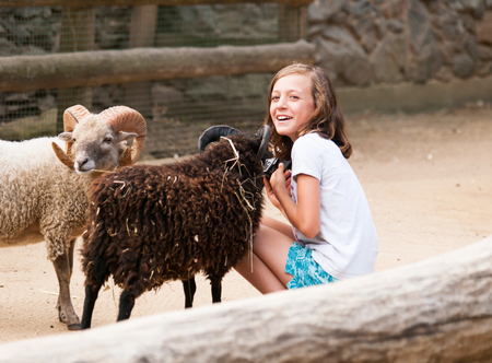 Young girl on farm craddle the goat with horns photo