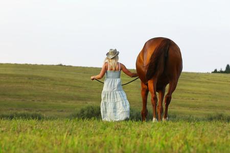 Blondine im Sommerkleid gehen langsam durch Wiese neben ihrem Pferd Standard-Bild - 85433503