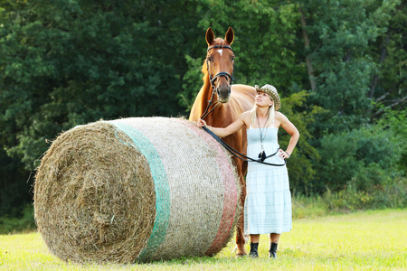 hayroll: Woman with her horse stay near hay roll on meadow