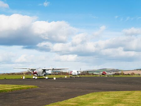 Small sport airplanes stay on runway in sunny day