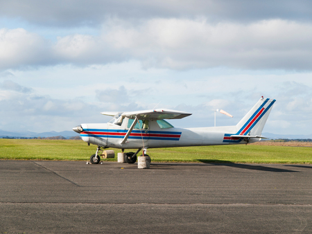 Small sport single-engine plane parked on runway Stock Photo