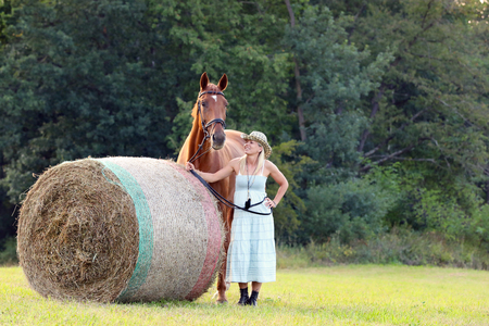 Woman with her horse stay near hay roll on meadow