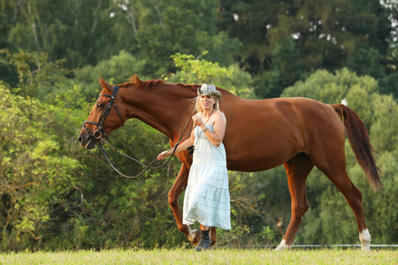 Woman in summer dress lead horse on pasture